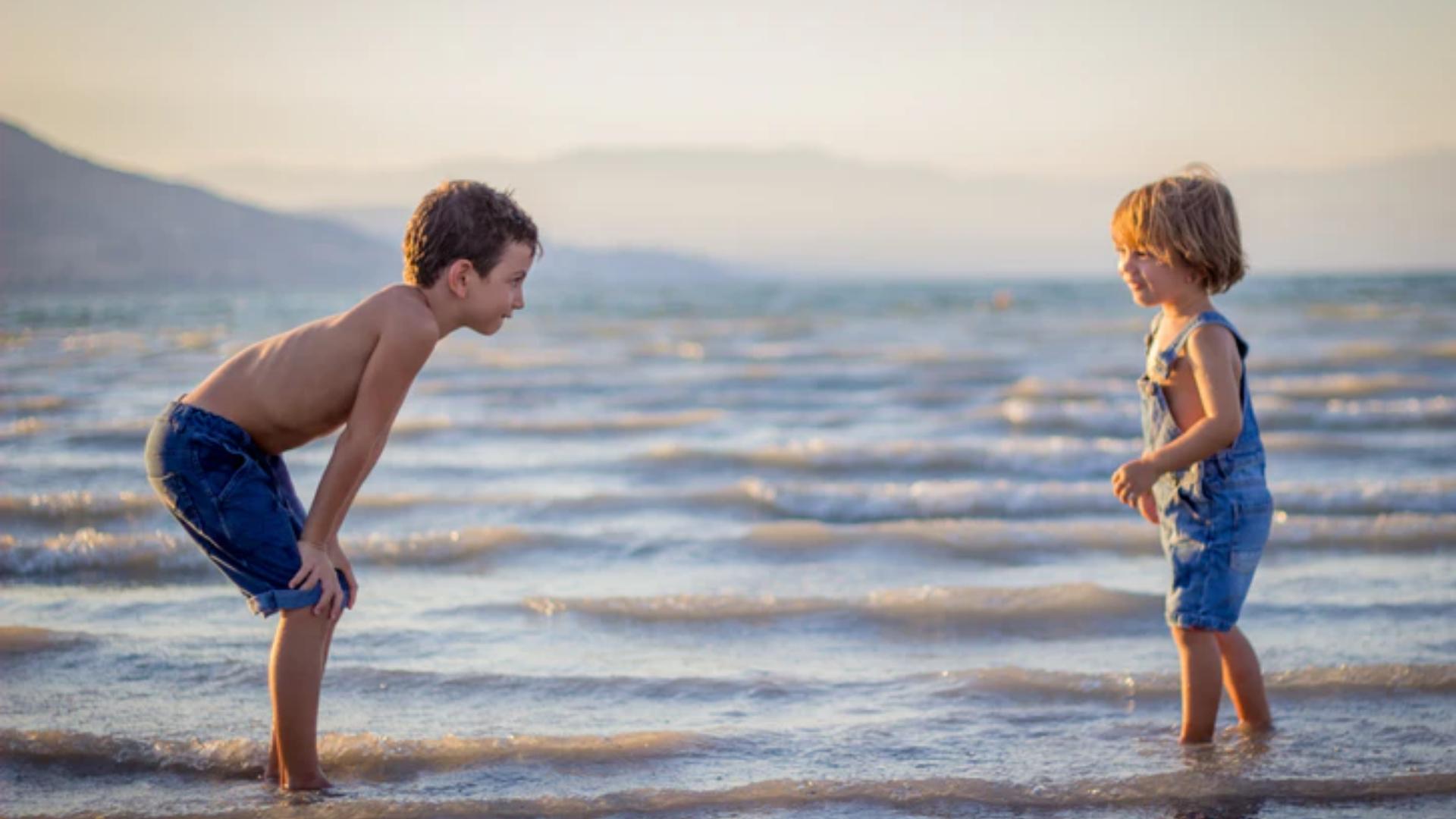 enfants à la plage les pieds dans l'eau
